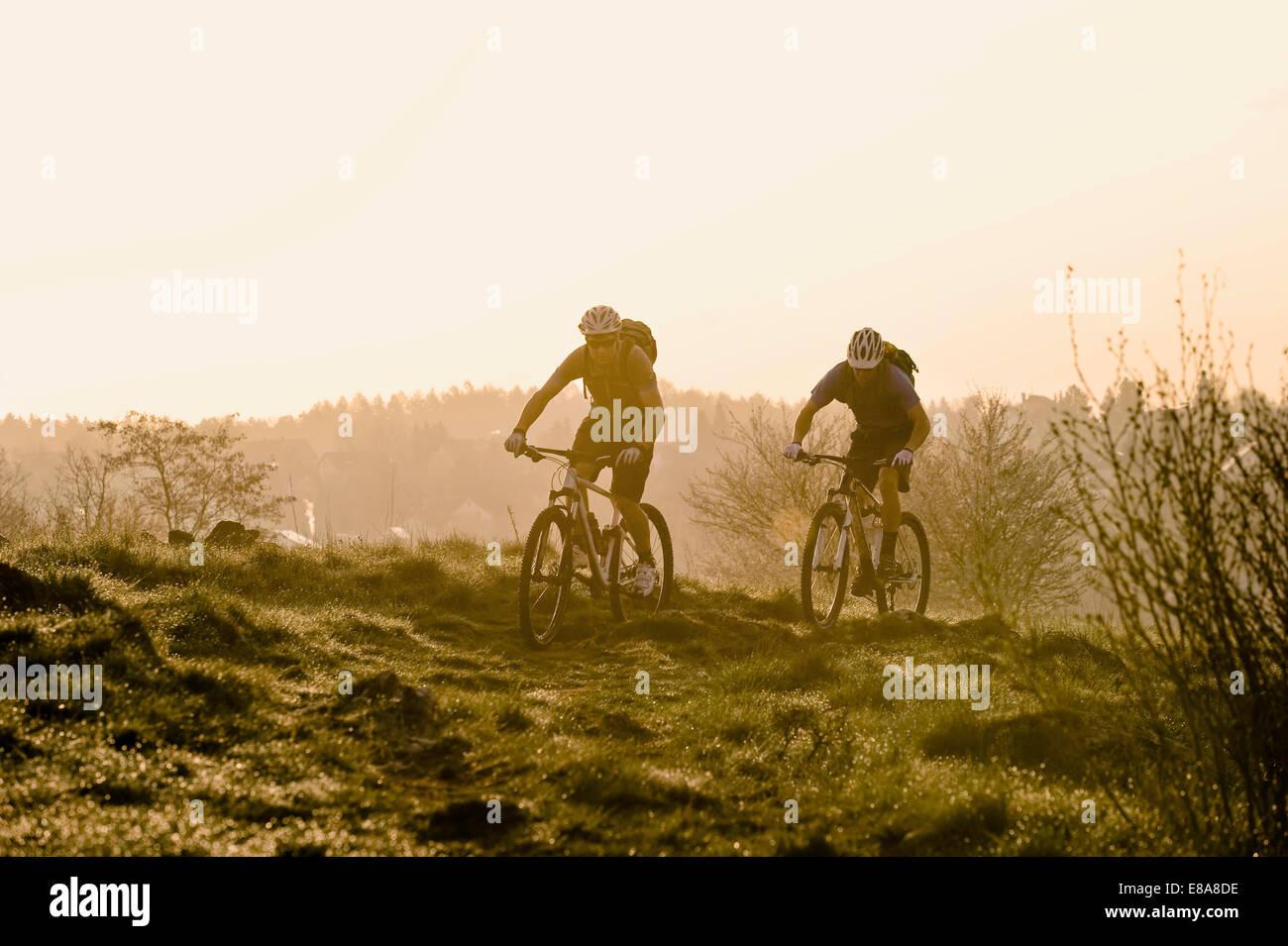 Los hombres jóvenes ir en bici al amanecer, Baviera, Alemania Imagen De Stock