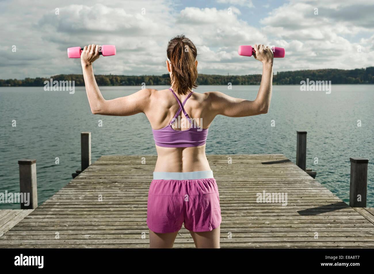Mujer entrenamiento con pesas, Woerthsee, Baviera, Alemania Imagen De Stock