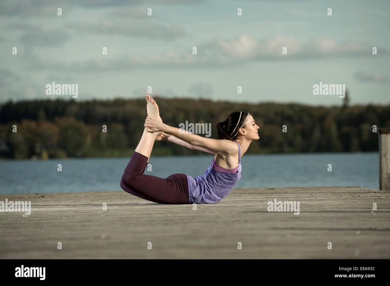 Mujer practicando yoga en jetty, Woerthsee, Baviera, Alemania Foto de stock