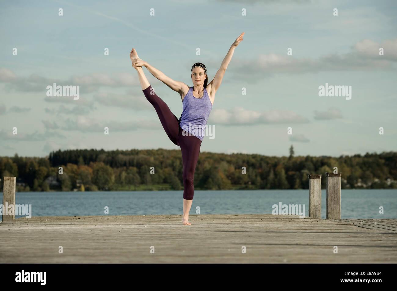 Mujer practicando yoga en jetty, Woerthsee, Baviera, Alemania Imagen De Stock