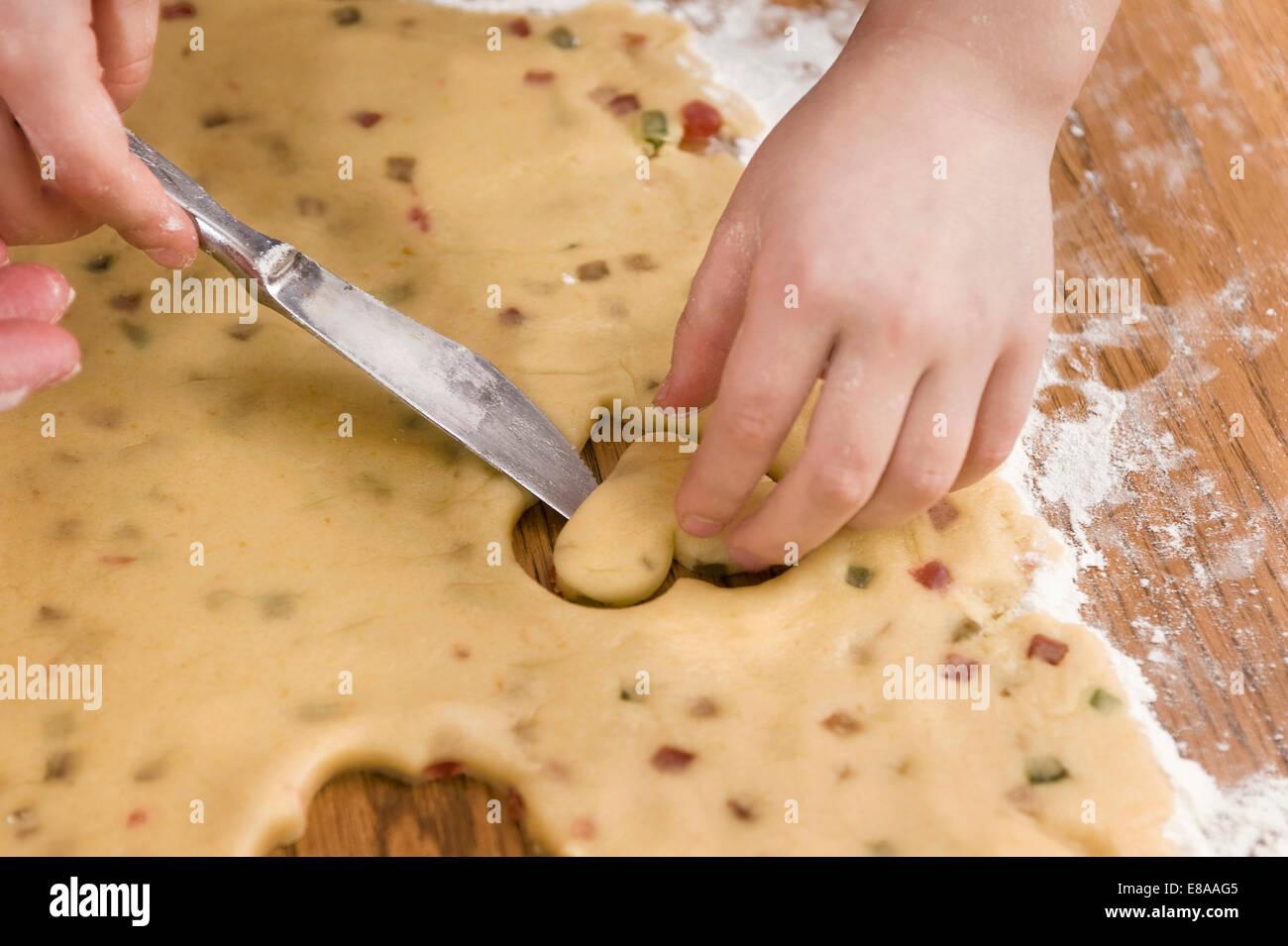La mano del hombre de corte con cuchilla de masa para galletas, cerrar Imagen De Stock