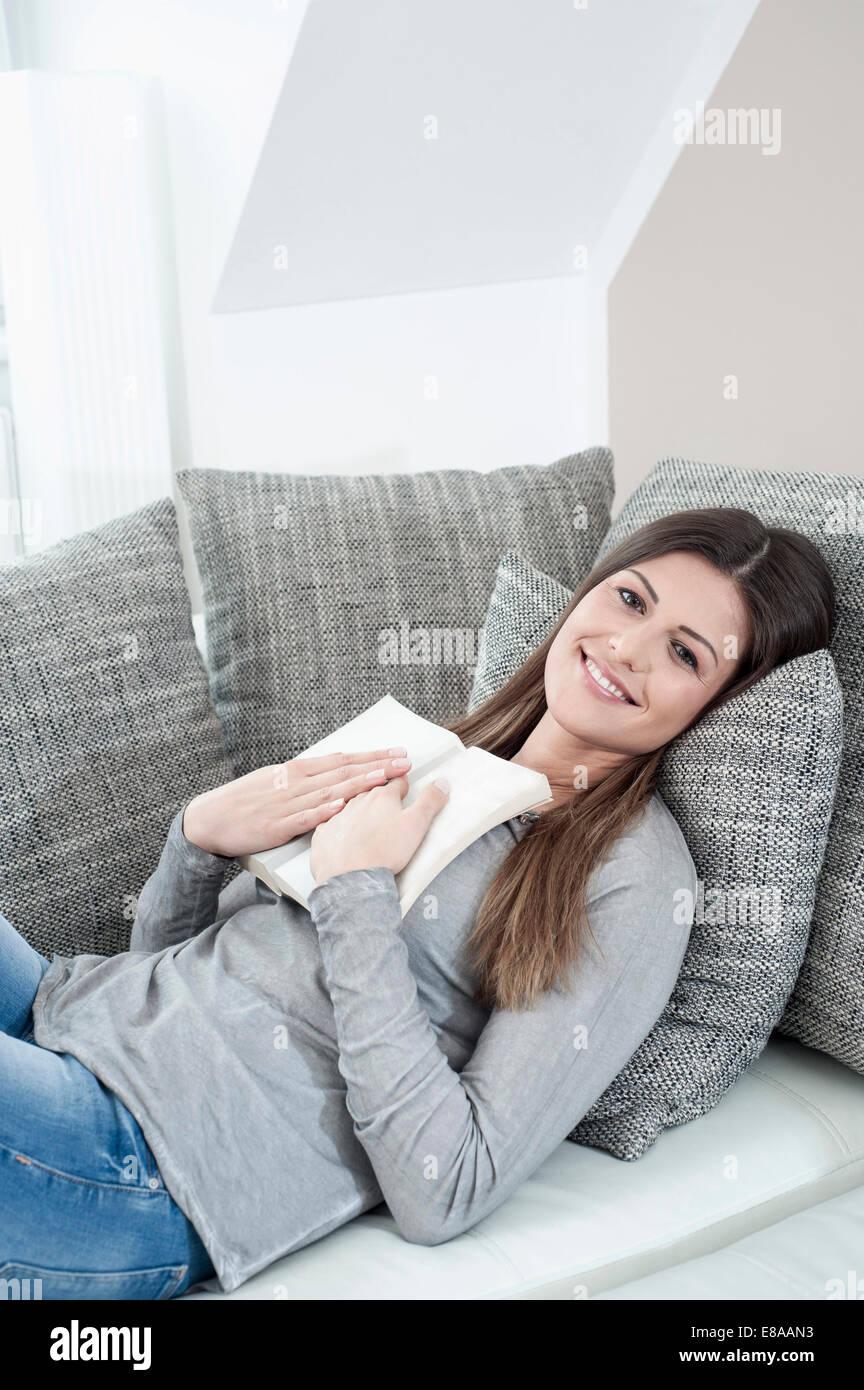 Retrato de mujer sonriente con libro abierto tumbado en el sofá en casa Foto de stock