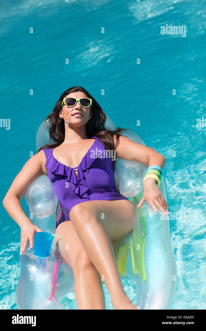 Mujer joven tomando el sol en la cama de aire en la piscina Foto de stock
