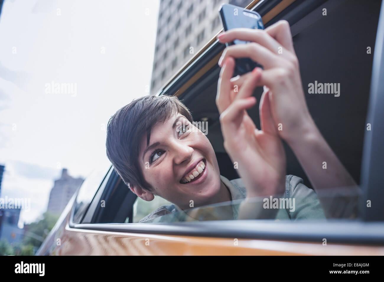 Mujer fotografiar en taxi amarillo, Nueva York, EE.UU. Imagen De Stock