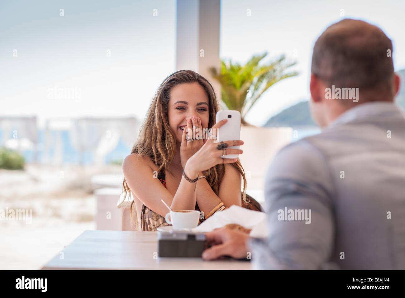 Mujer joven tomando fotografía de novio en smartphone en playa, Castiadas, Cerdeña, Italia Imagen De Stock