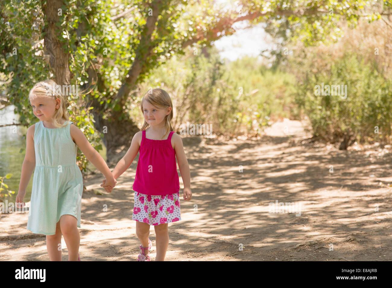 Dos hermanas jóvenes paseando y tomados de la mano en la orilla Foto de stock