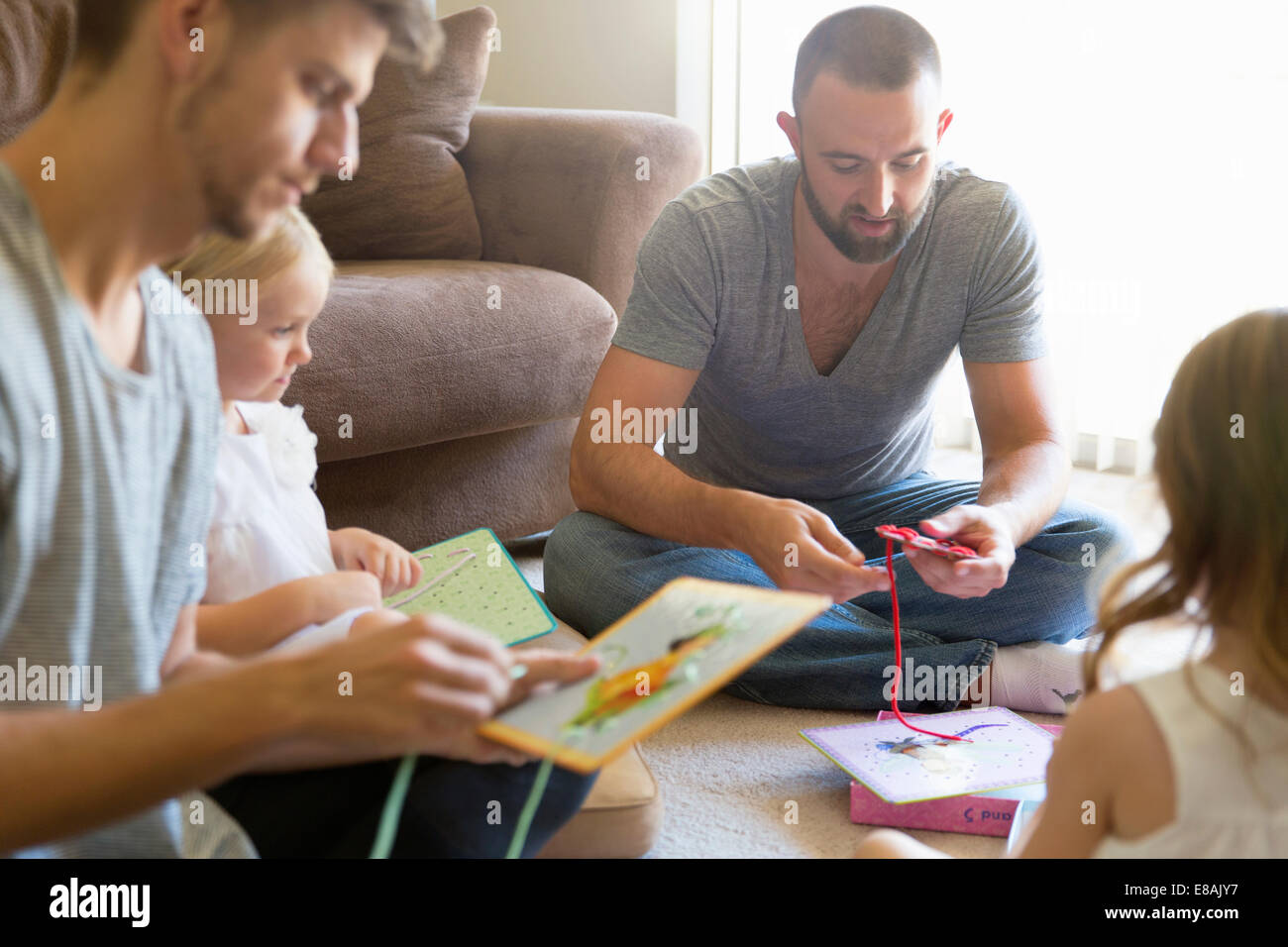 La pareja masculina y dos hijas enhebrado de libros ilustrados sobre el suelo de la sala de estar Imagen De Stock