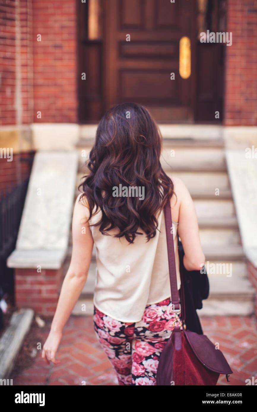 Mujer caminando hacia las escaleras a la puerta delantera Imagen De Stock