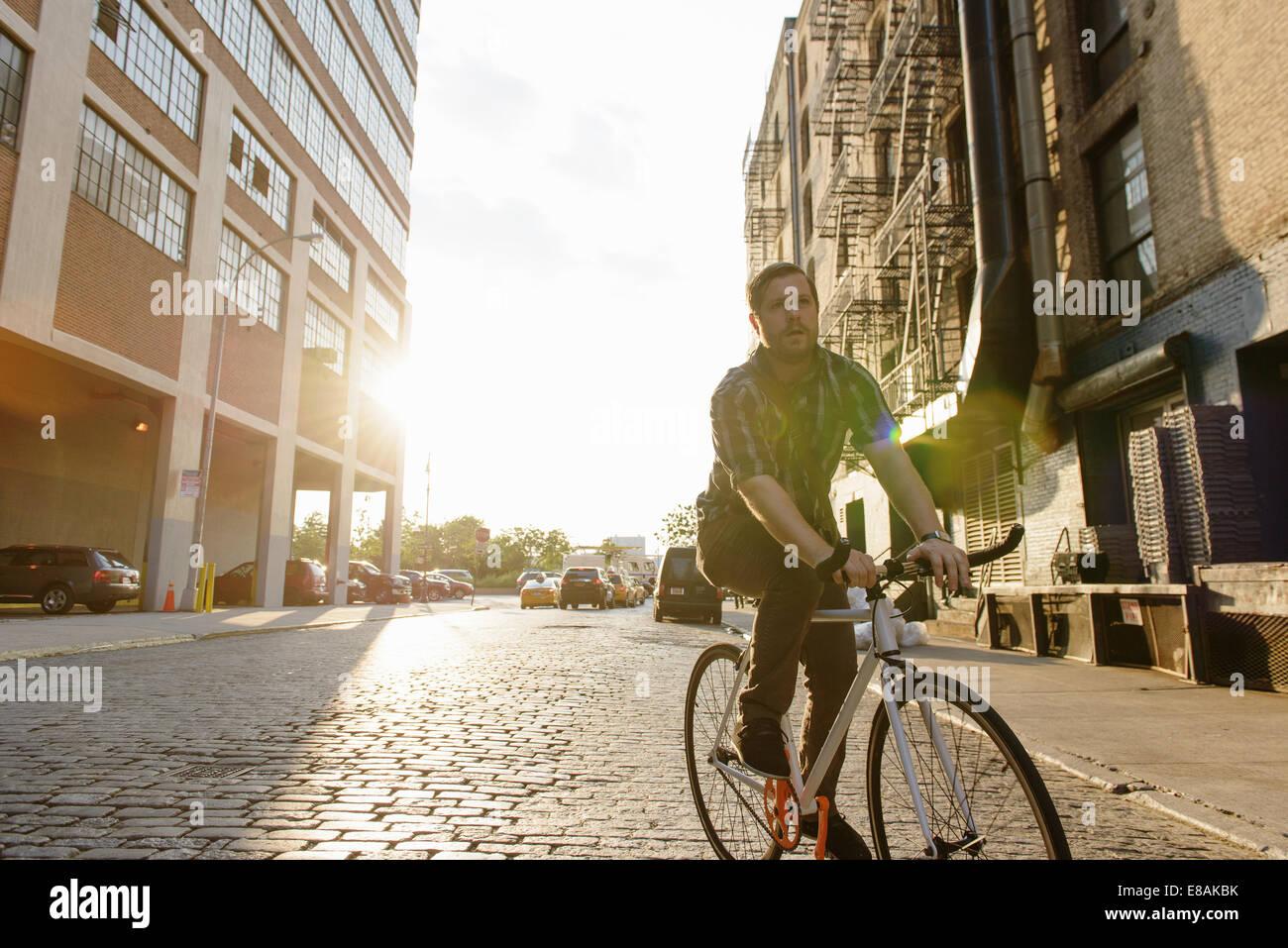 Messenger masculino en bicicleta a lo largo de las calles de la ciudad Foto de stock
