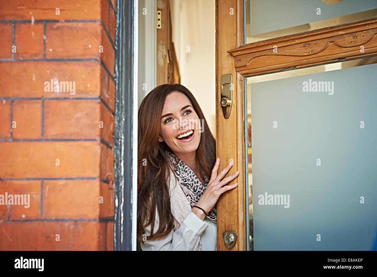 Mujer abriendo la puerta delantera Imagen De Stock