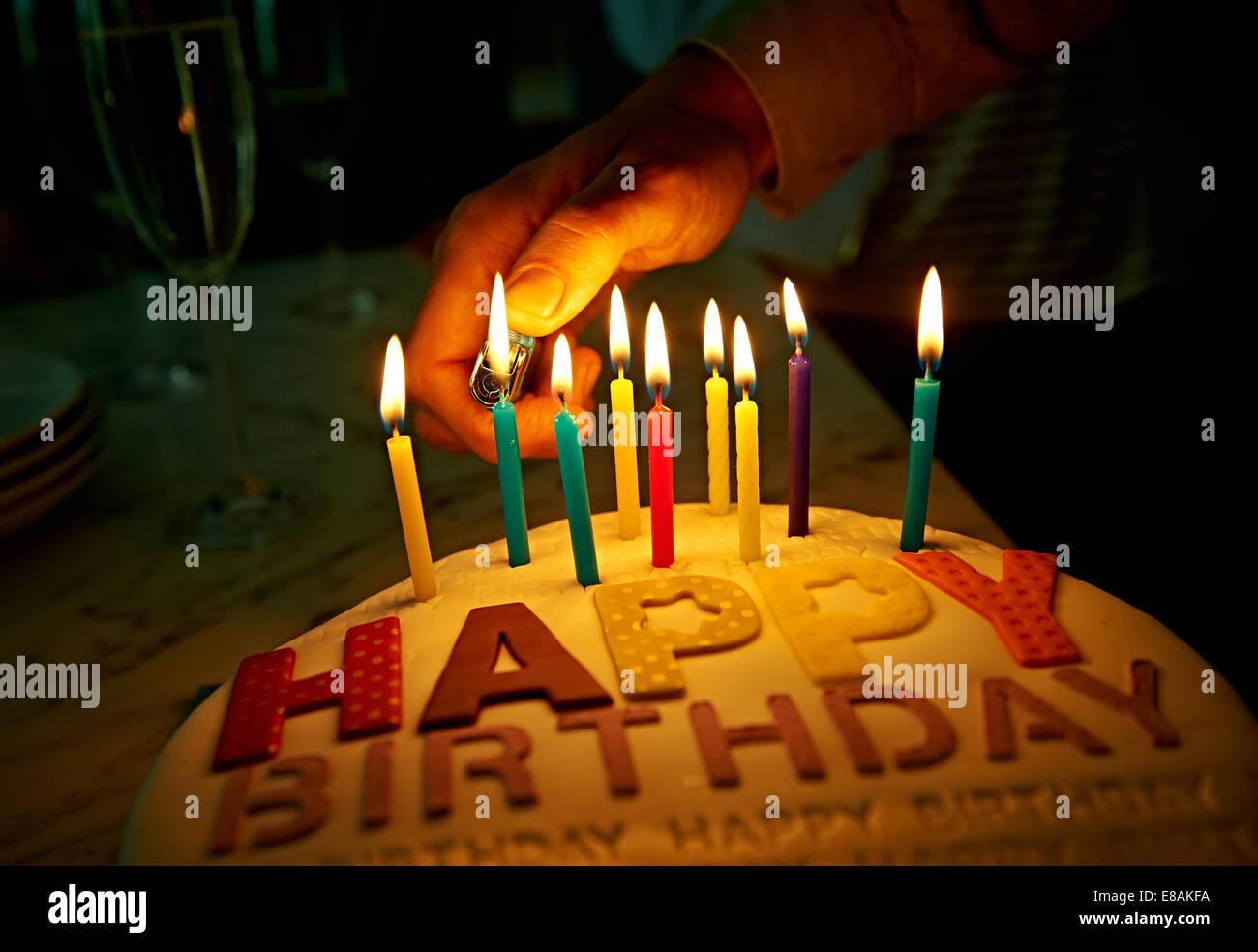 Mano encendiendo velas en la tarta de cumpleaños Imagen De Stock