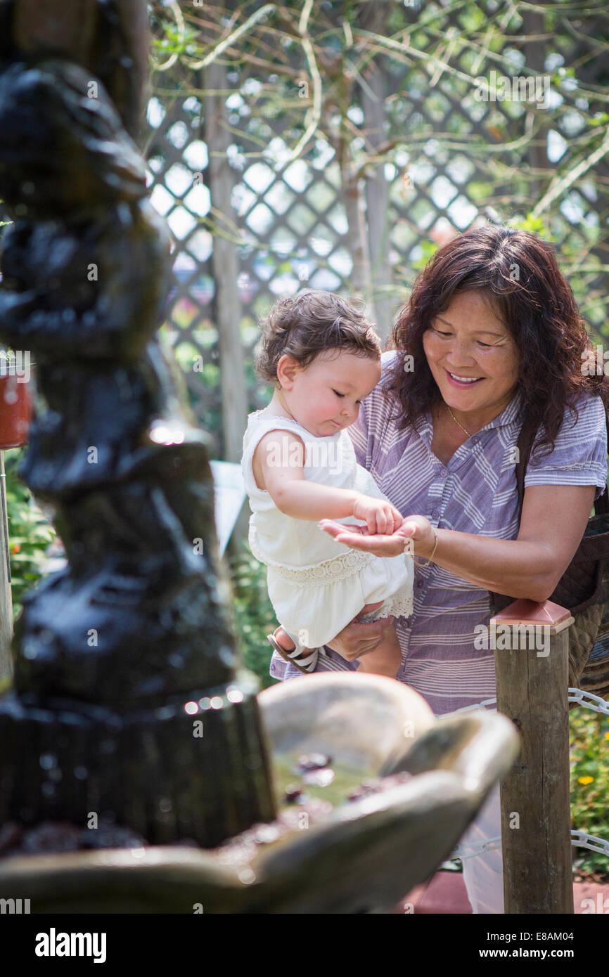 Abuela y nieta materna con estanque en zoo Imagen De Stock