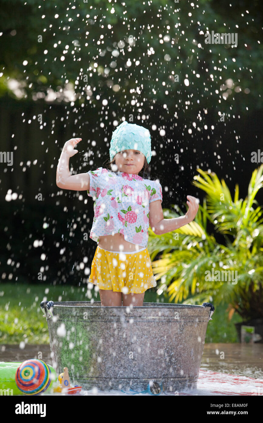 Chica de pie en el baño de burbujas en el jardín las salpicaduras de pompas de jabón Imagen De Stock