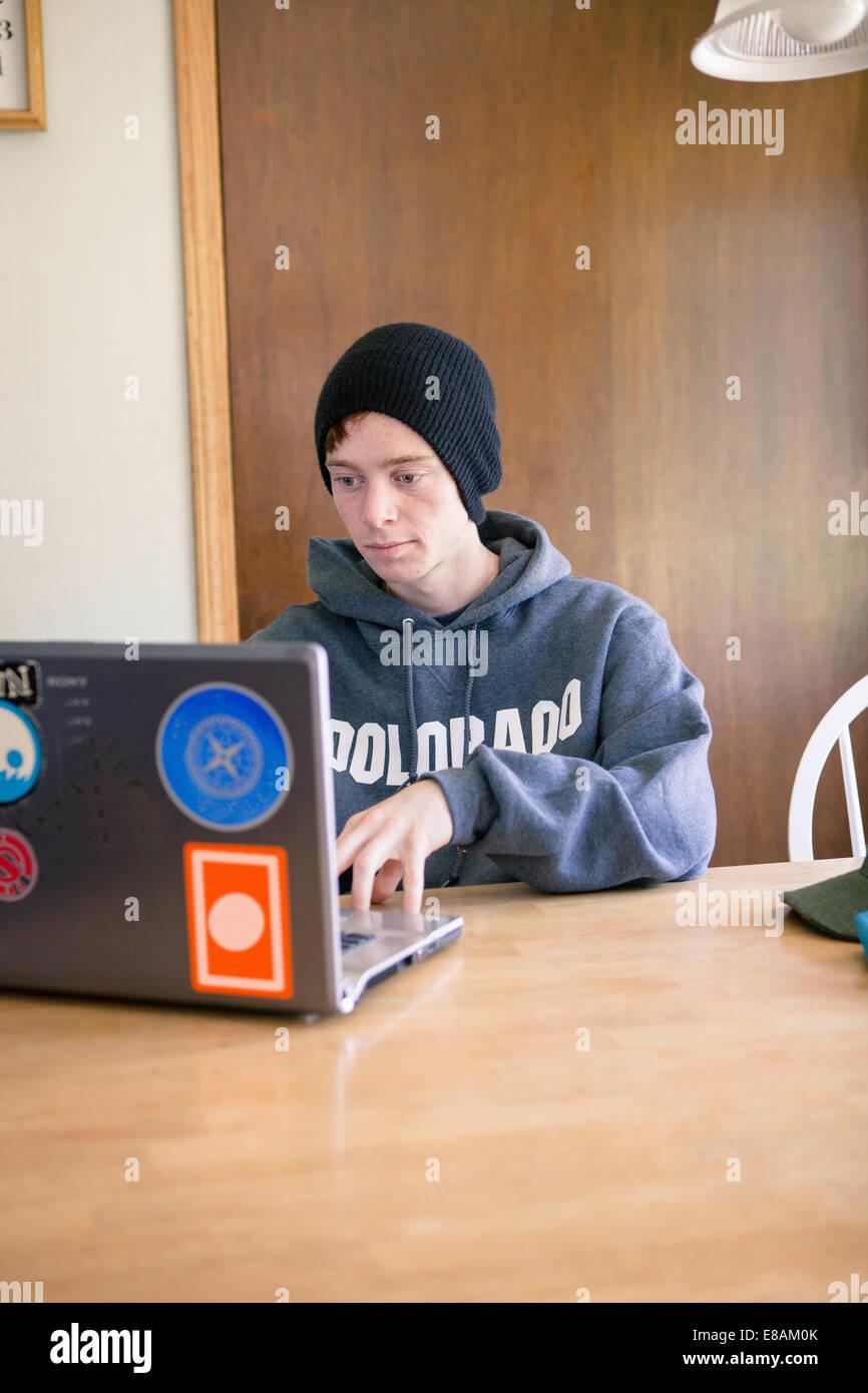 Adolescente sentado en la mesa de comedor utilización portátil Imagen De Stock