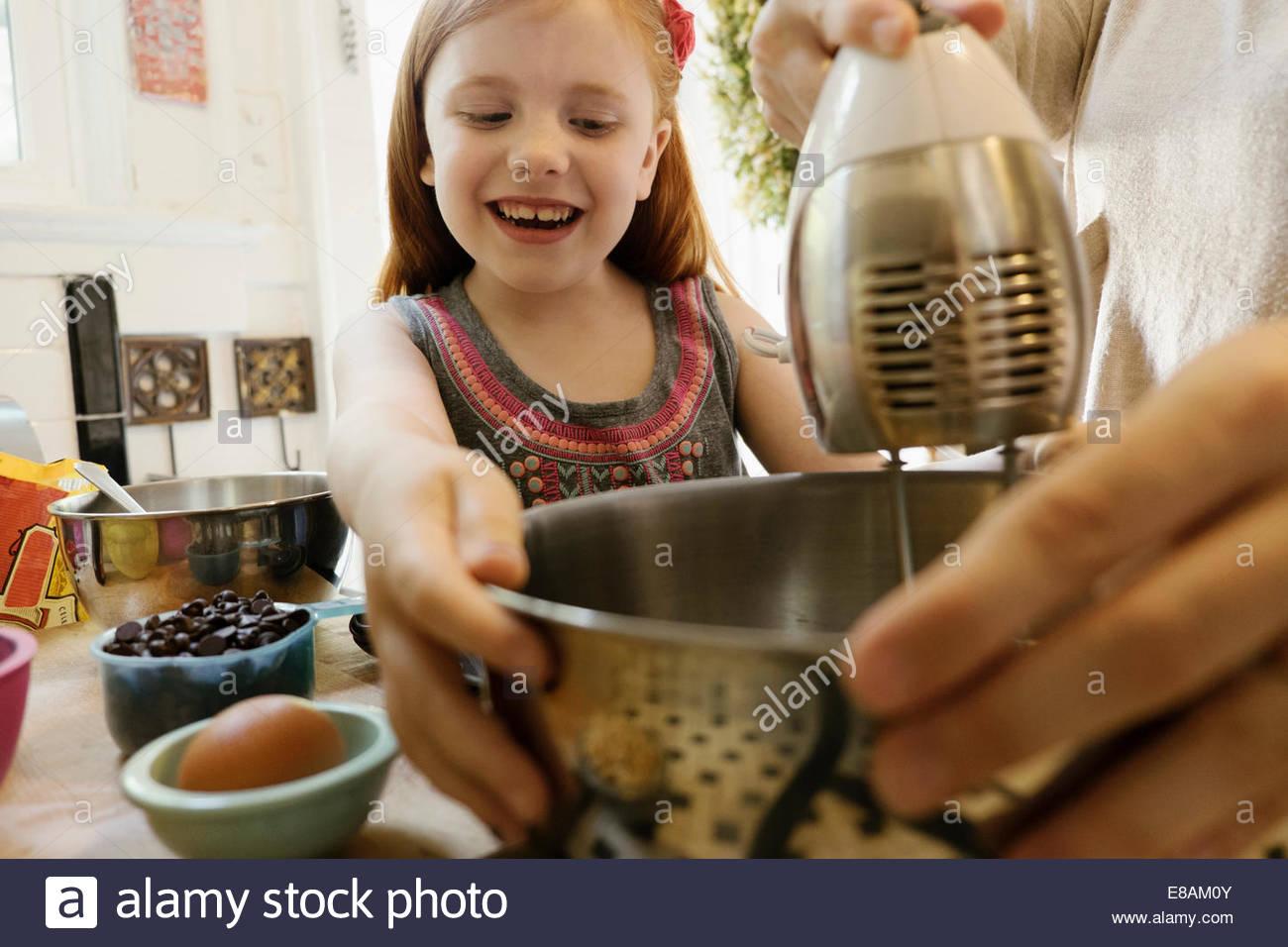 Niña Madre dando una mano en la cocina Imagen De Stock