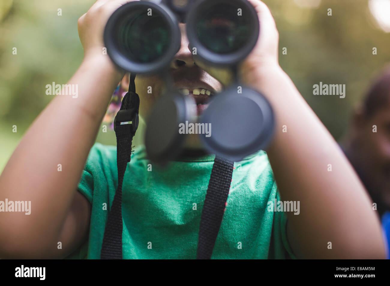 Cerca de niña mirando a través de binoculares en bosque campamento ecológico Imagen De Stock