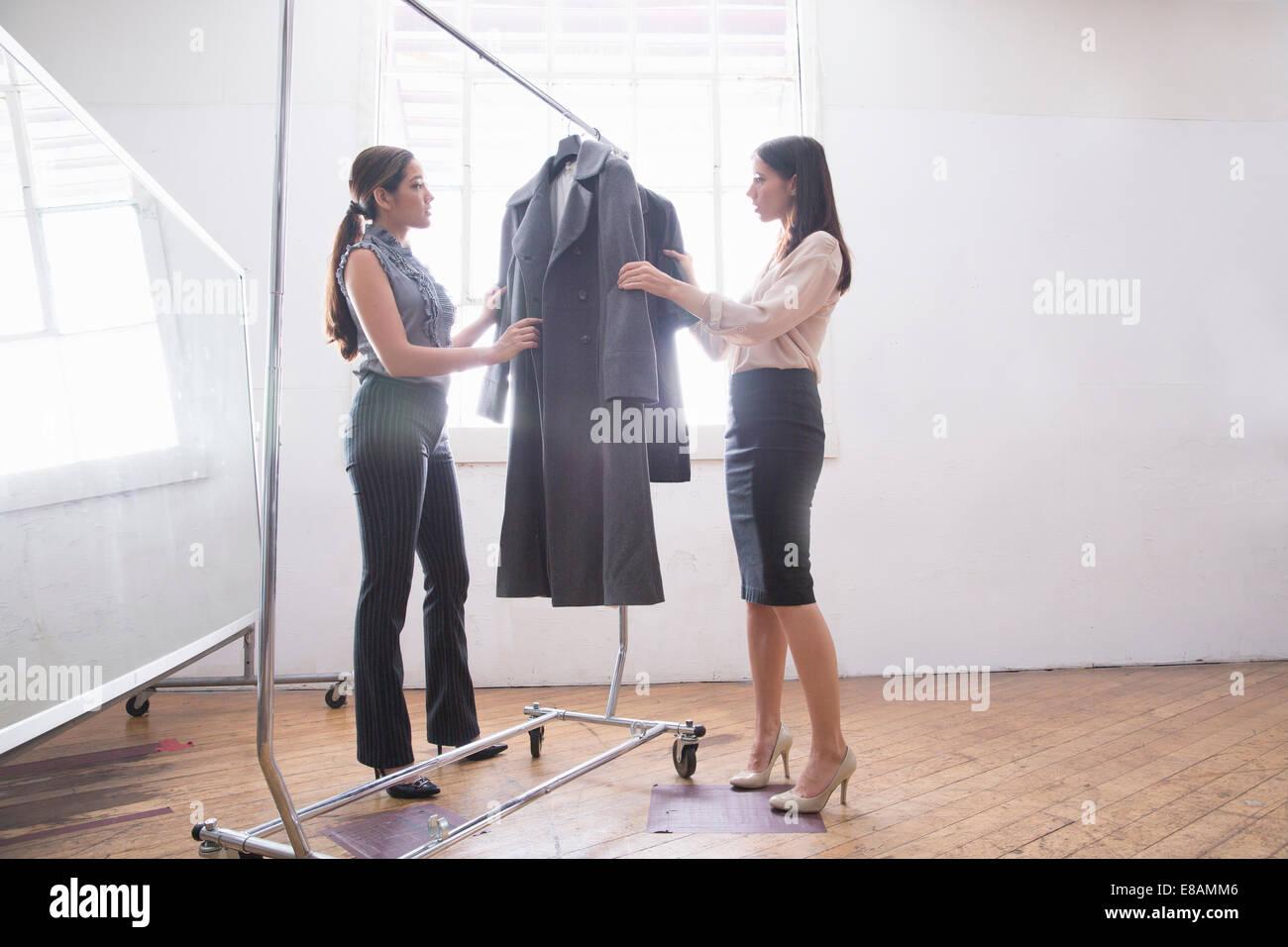 Empresarias eligiendo ropas elegantes de rampa de ropa Imagen De Stock