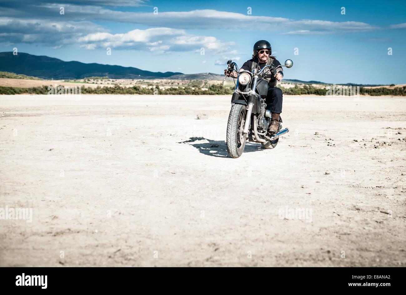 Hombre maduro montando motocicleta por árida llanura, Cagliari, Cerdeña, Italia Imagen De Stock