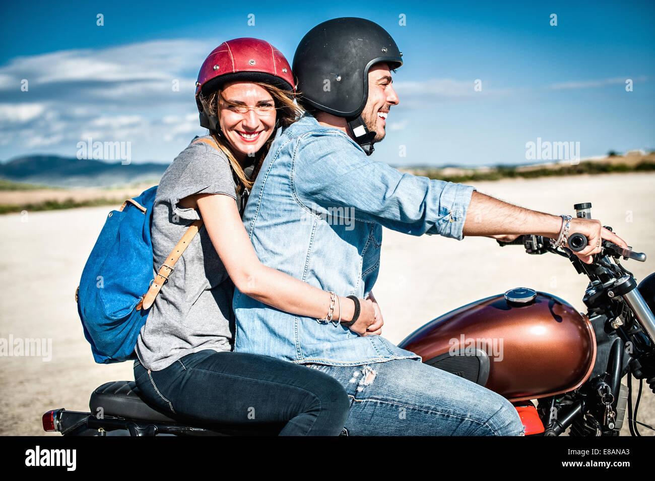 Pareja adulta media montando motocicleta en la árida llanura, Cagliari, Cerdeña, Italia Imagen De Stock