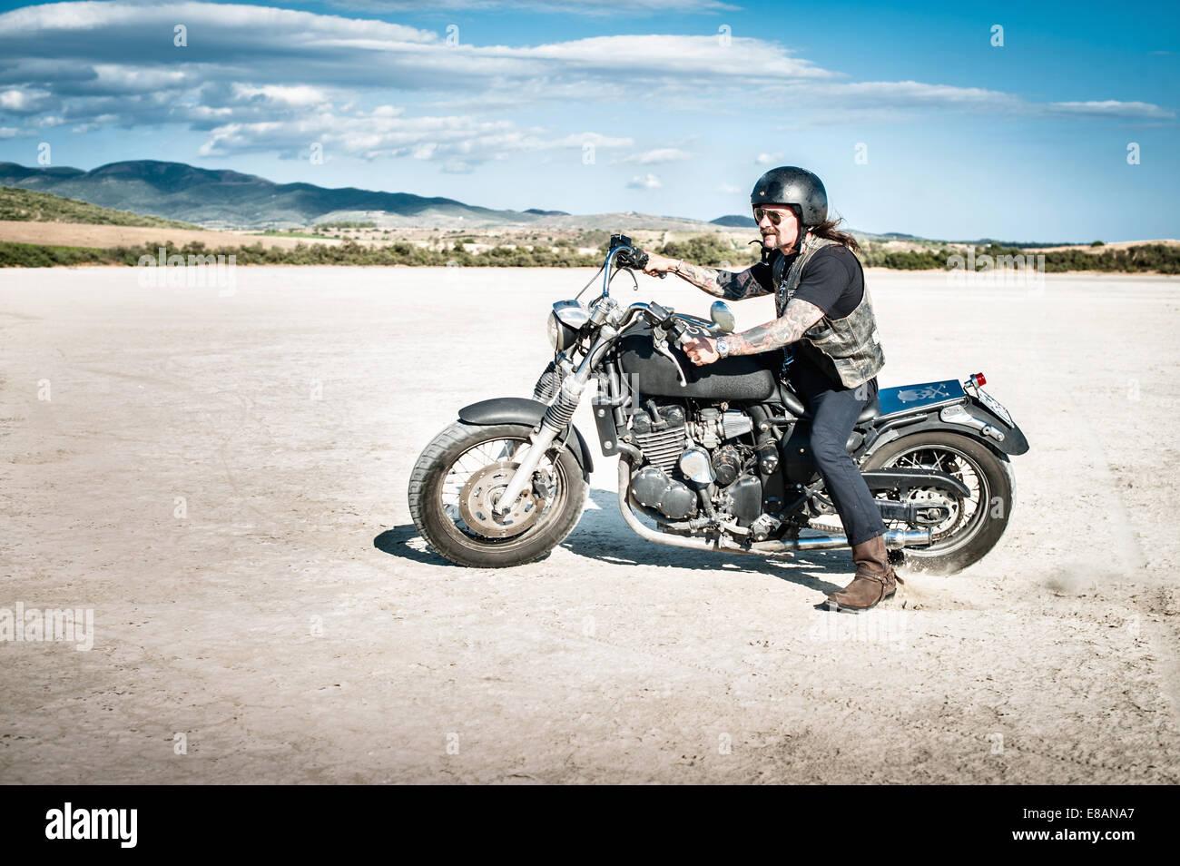 Motociclista macho en la árida llanura, Cagliari, Cerdeña, Italia Imagen De Stock