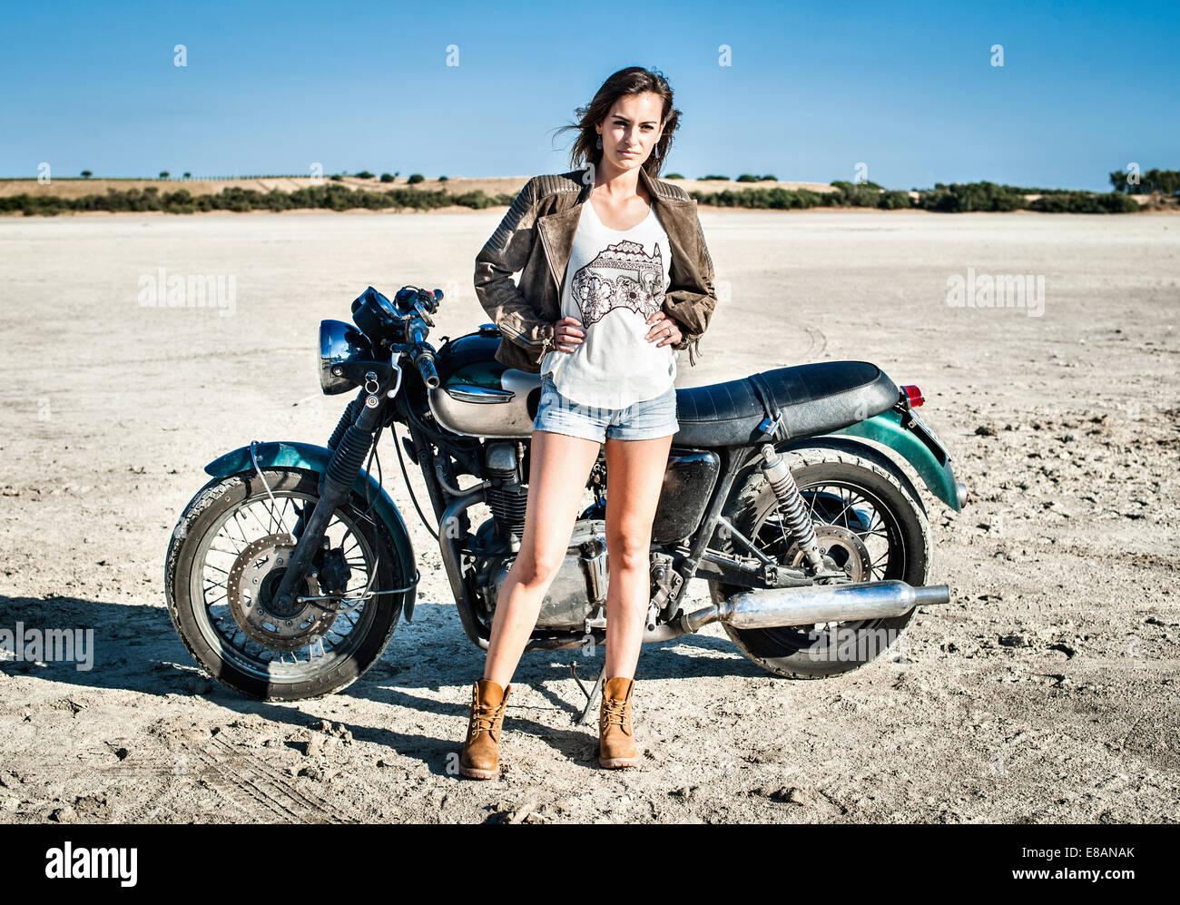 Retrato de mujer motociclista en la árida llanura, Cagliari, Cerdeña, Italia Imagen De Stock