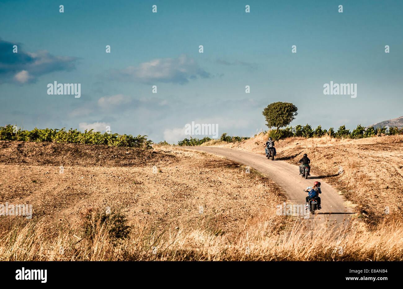 Vista trasera de cuatro amigos montando motos en caminos rurales, Cagliari, Cerdeña, Italia Imagen De Stock