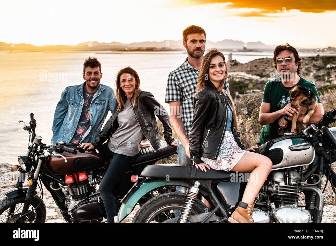 Retrato de cinco amigos de motociclismo en la costa al atardecer, Cagliari, Cerdeña, Italia Imagen De Stock