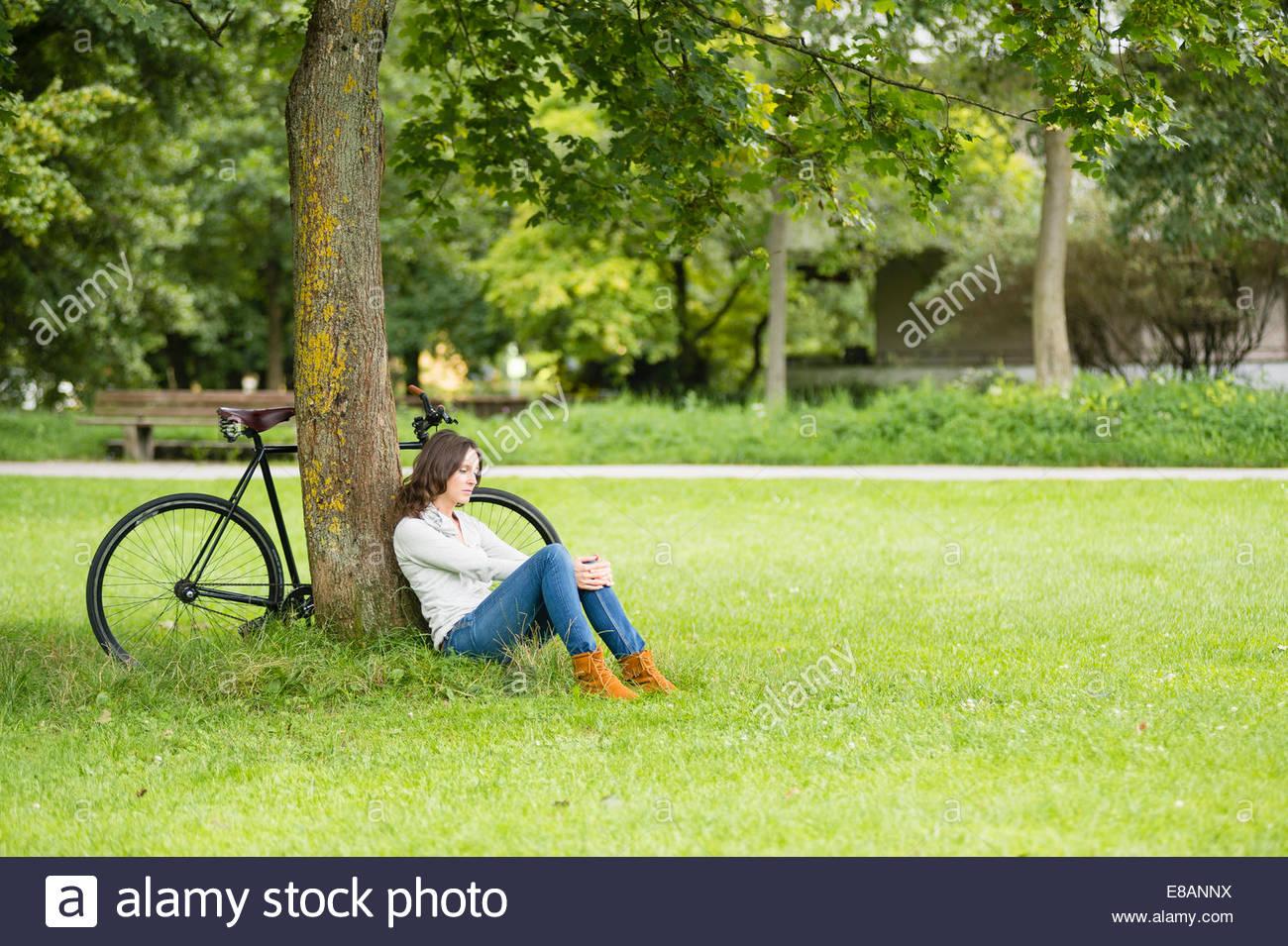 Mujer adulta media ciclista sentado contra el árbol de estacionamiento Imagen De Stock