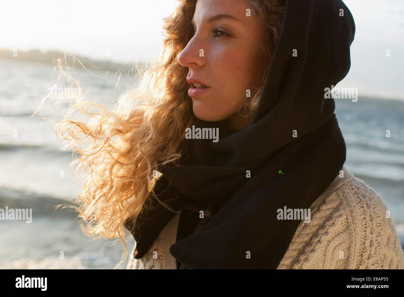 Mujer todo envuelto en playa ventosa Foto de stock