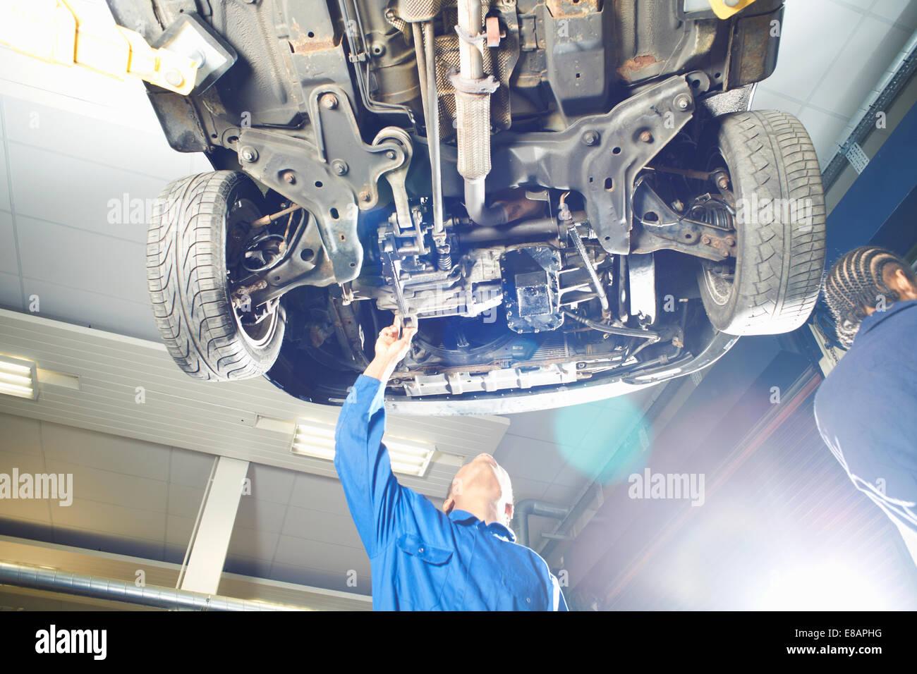 Estudiante universitario masculino mirando hacia arriba a un automóvil en el garaje taller Imagen De Stock