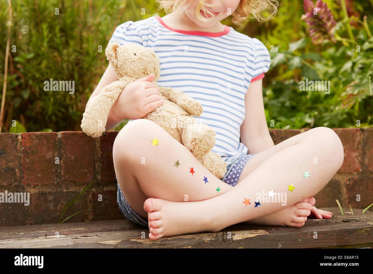 Chica en el asiento de jardín con star pegatinas en las piernas Foto de stock