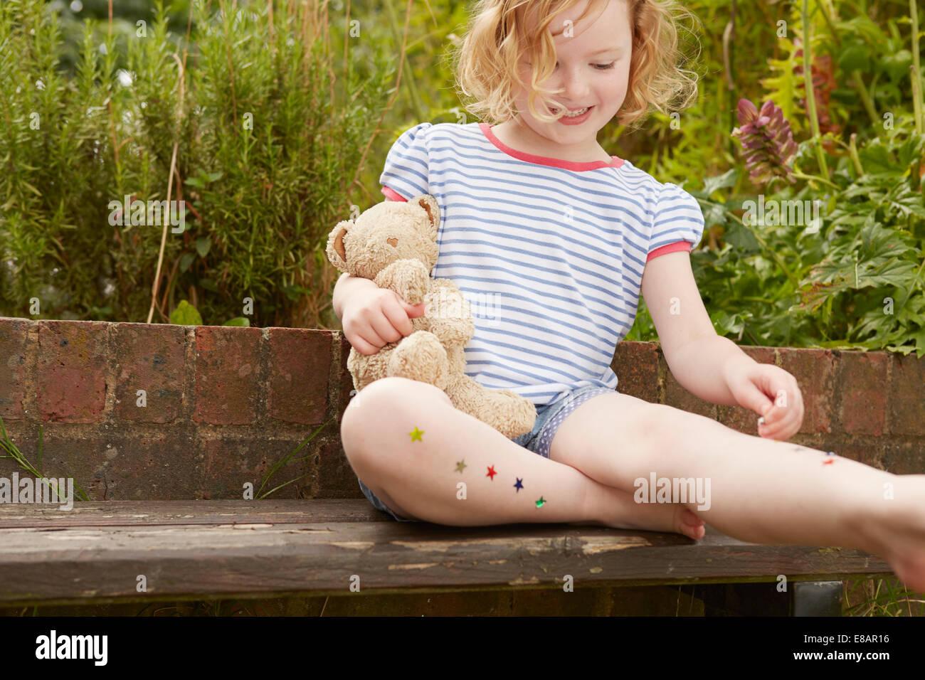 Chica pegada estrellas en las piernas sobre el asiento de jardín Foto de stock