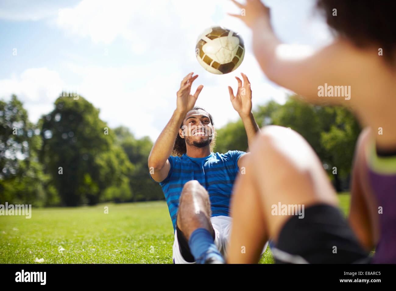 Pareja joven formación con una pelota de fútbol en el parque Imagen De Stock