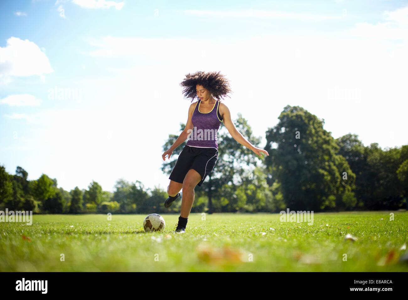 Mujer joven pateando una pelota de fútbol en el parque Foto de stock