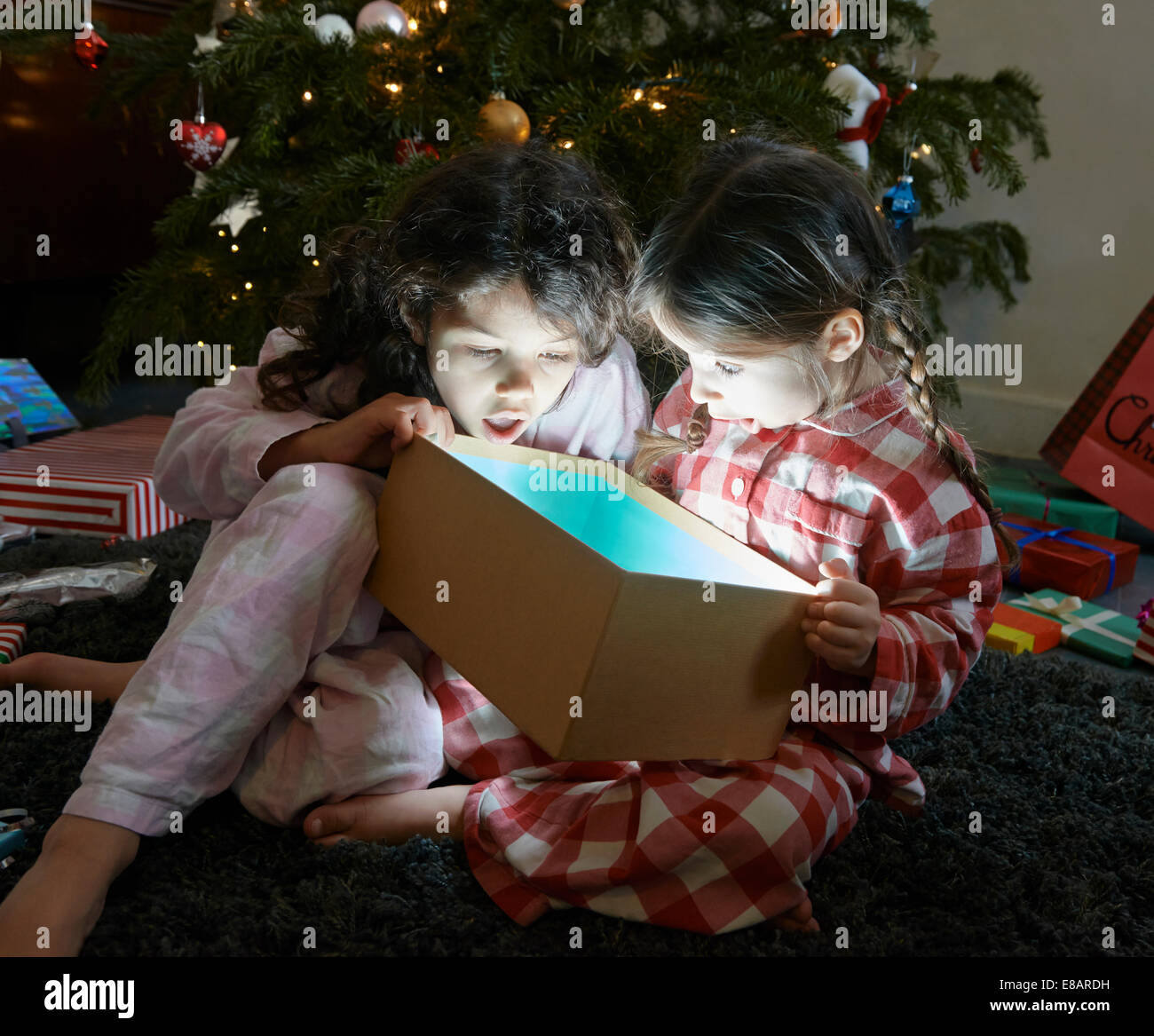 Dos hermanas atónito en desenvolver brillante caja de regalo de navidad Imagen De Stock