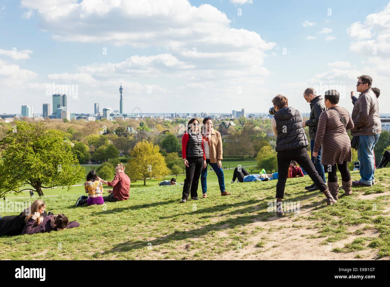 La gente fotografiando amigos de Primrose Hill con el horizonte de la ciudad de Londres en la distancia, Inglaterra, Imagen De Stock