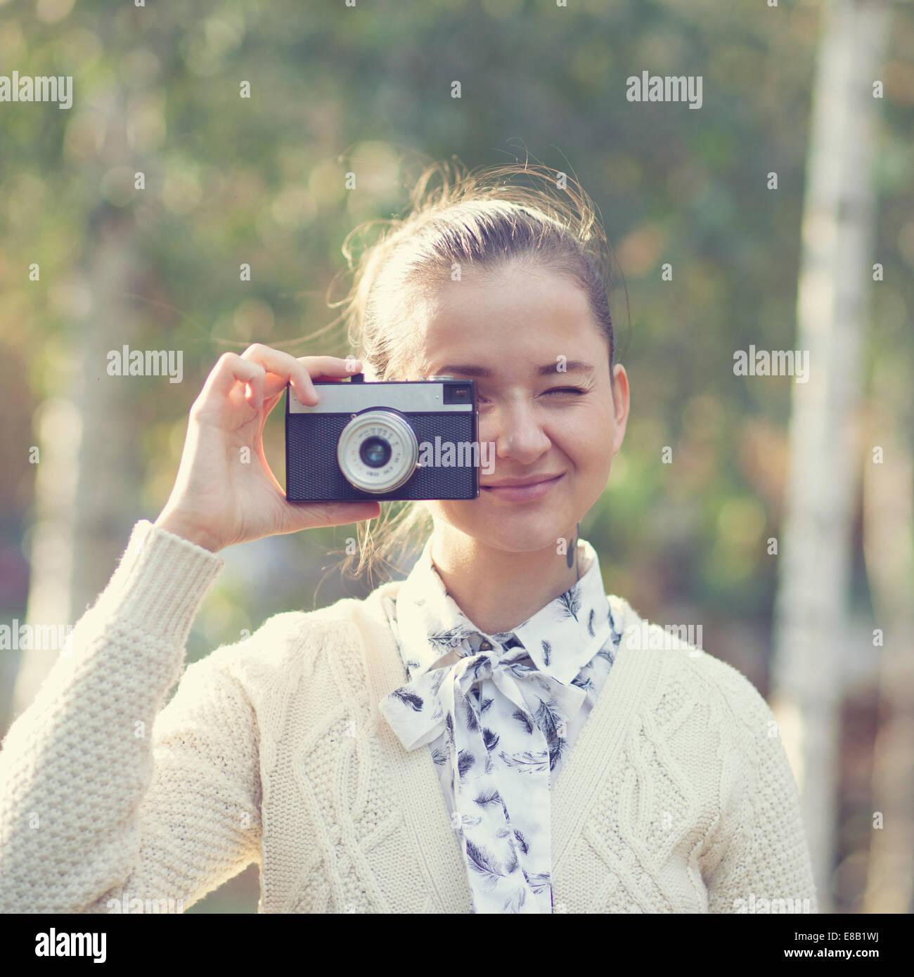 Hipster chica dispara en cámara de cine al aire libre Imagen De Stock