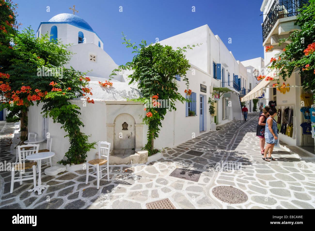 Fuente de agua griega y la iglesia de cúpula azul en las calles encaladas de la ciudad de Parikia, en la isla Imagen De Stock
