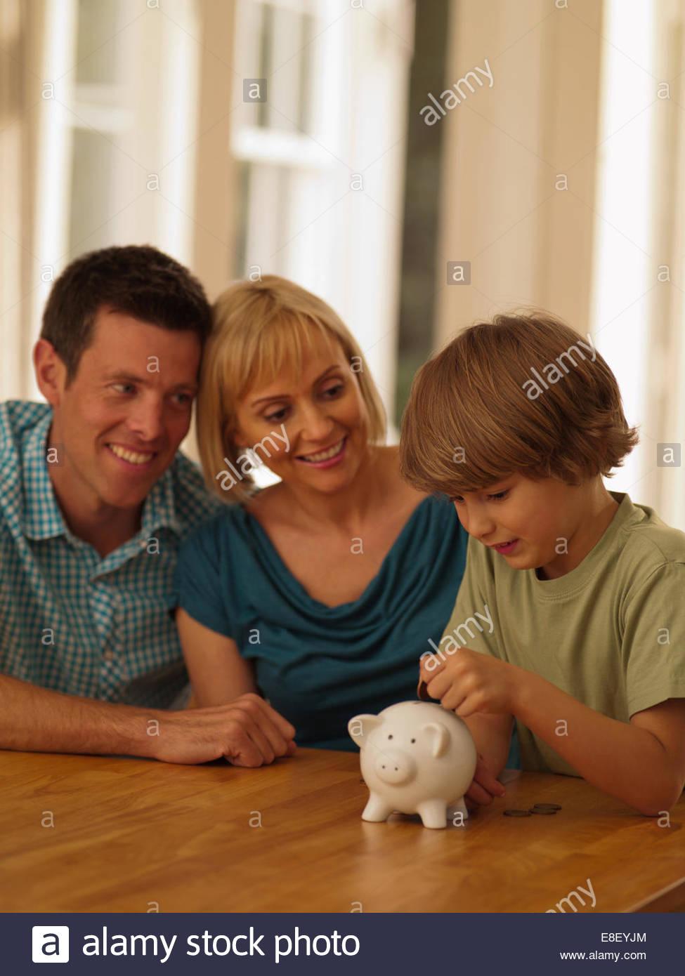 Los padres viendo hijo poner la moneda en la alcancía Imagen De Stock
