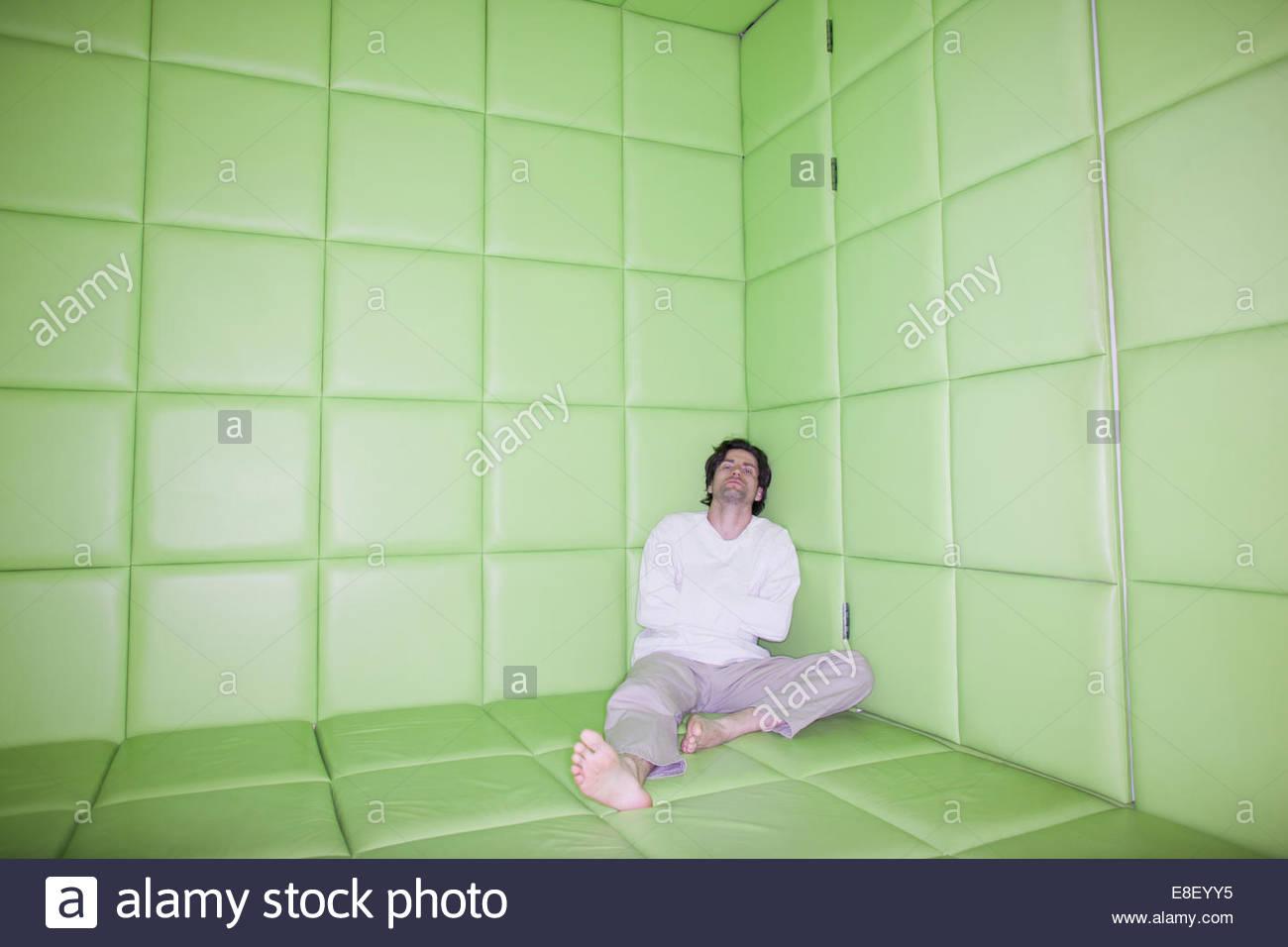 Hombre sentado con las piernas en la habitación acolchada Imagen De Stock