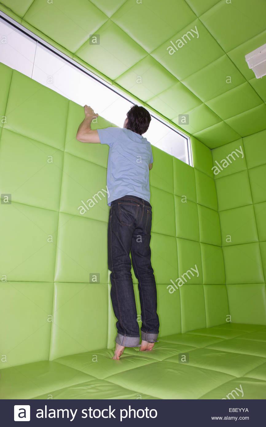 El hombre llega a mirar por la ventana en la habitación acolchada Imagen De Stock