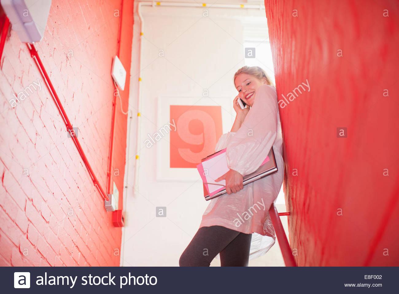 La empresaria sonriente Celebración carpetas y hablando por teléfono celular en la escalera Imagen De Stock