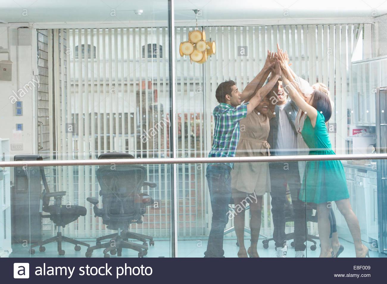 Gente de negocios entusiasmados con los brazos levantados en la ventana Imagen De Stock