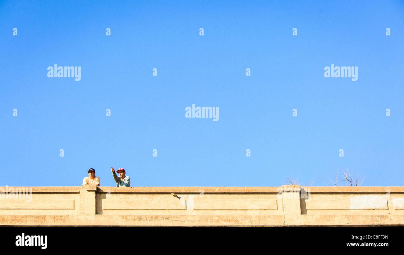 Dos hombres de pie en el puente Imagen De Stock