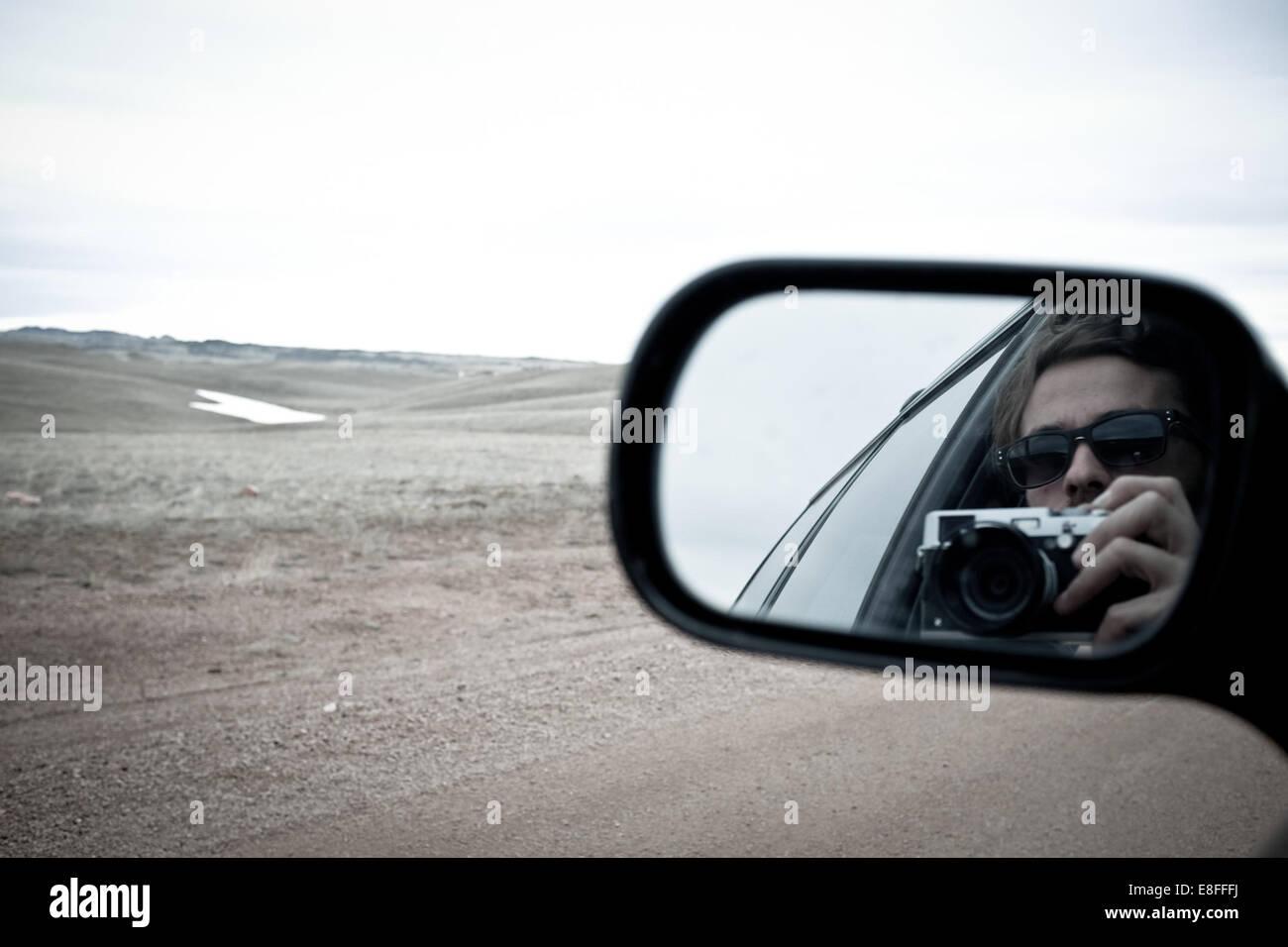 Mujer reflejando en el espejo lateral Imagen De Stock