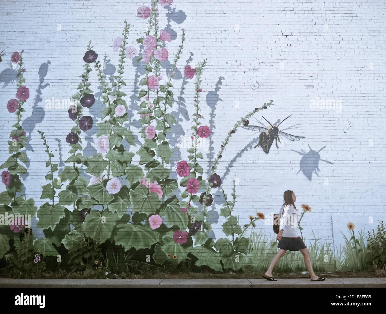 Mujer caminando por la pared florido Imagen De Stock