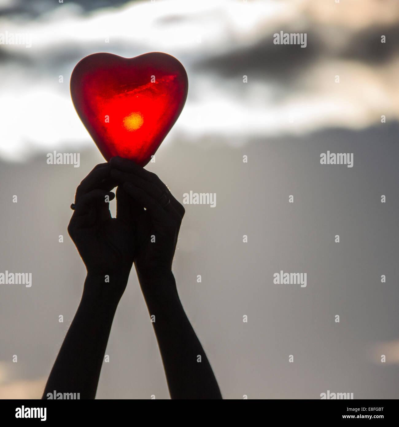 Manos de mujer sosteniendo un objeto con forma de corazón Imagen De Stock
