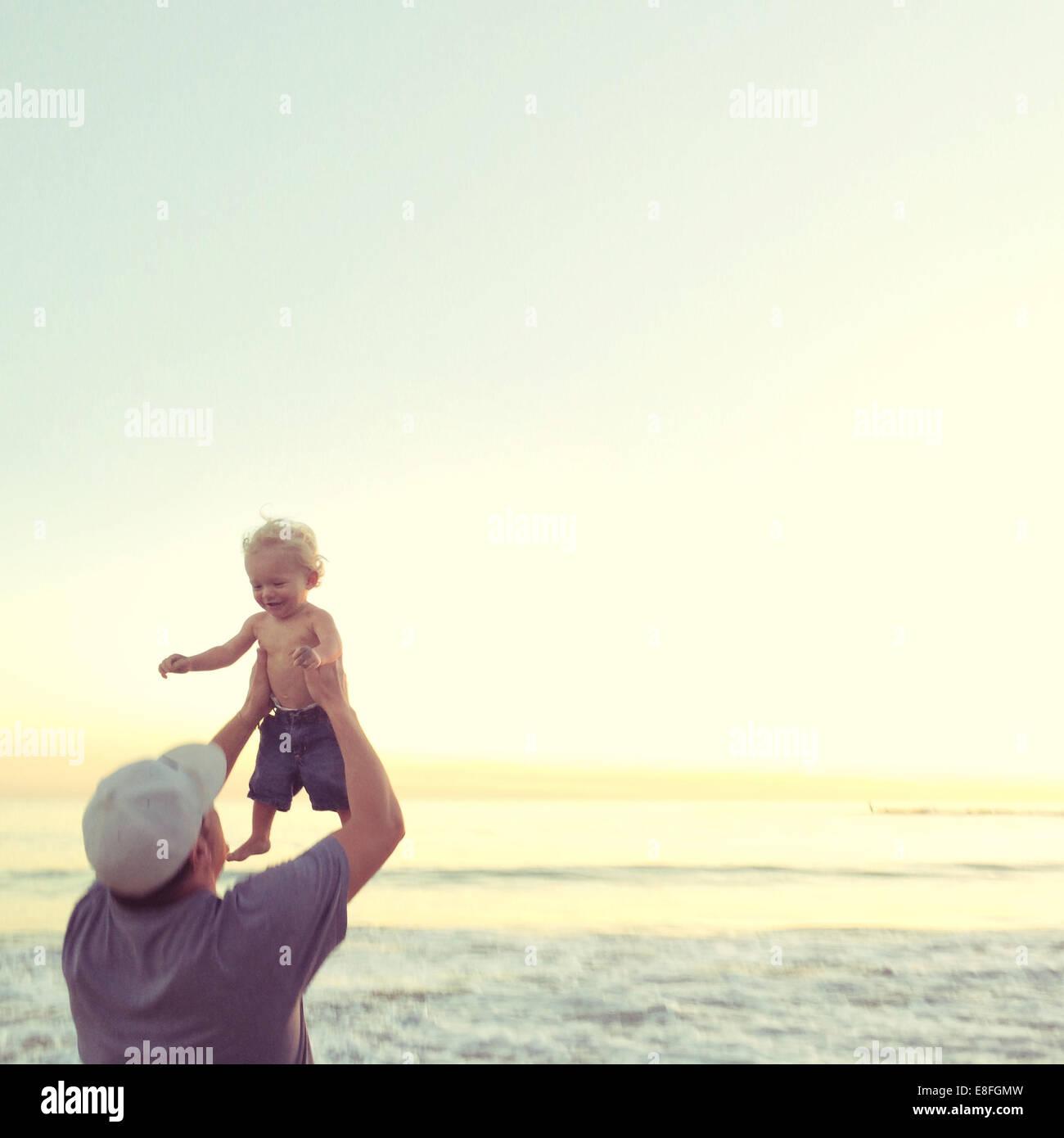Padre levantando su hijo en el aire en el Beach, California, Estados Unidos, EE.UU. Imagen De Stock