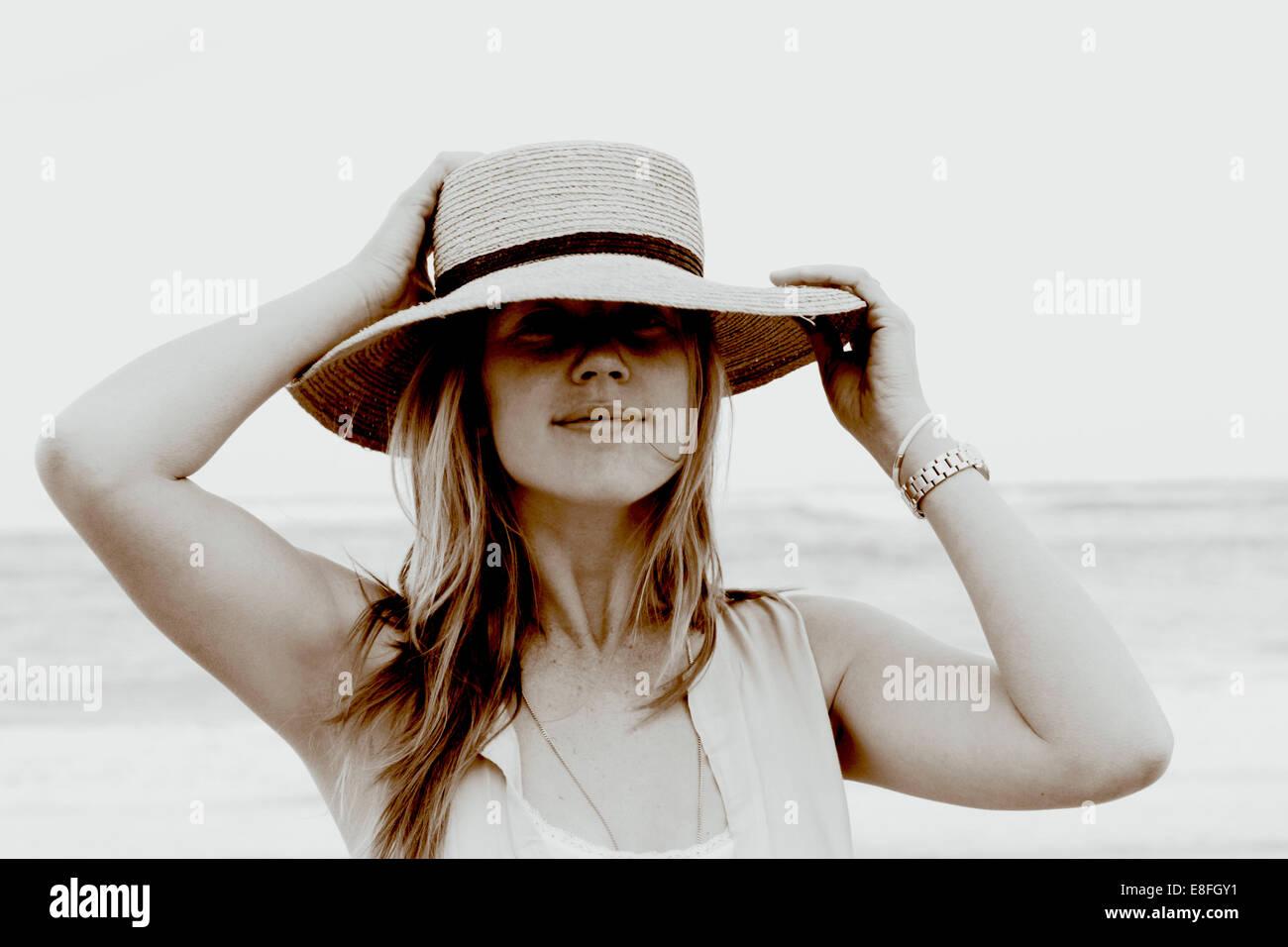 Retrato de una mujer de pie en la playa sosteniendo su sombrero Imagen De Stock
