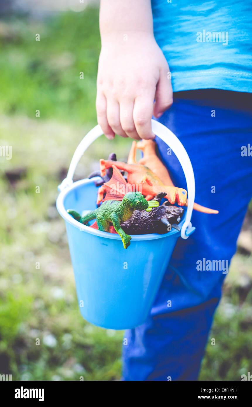 Niño sosteniendo la cuchara de plástico juguetes de dinosaurios Imagen De Stock
